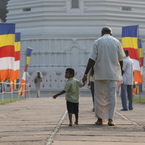 Local grandfather and grandson visiting the Temple of the Tooth, Kandy. Sri Lanka